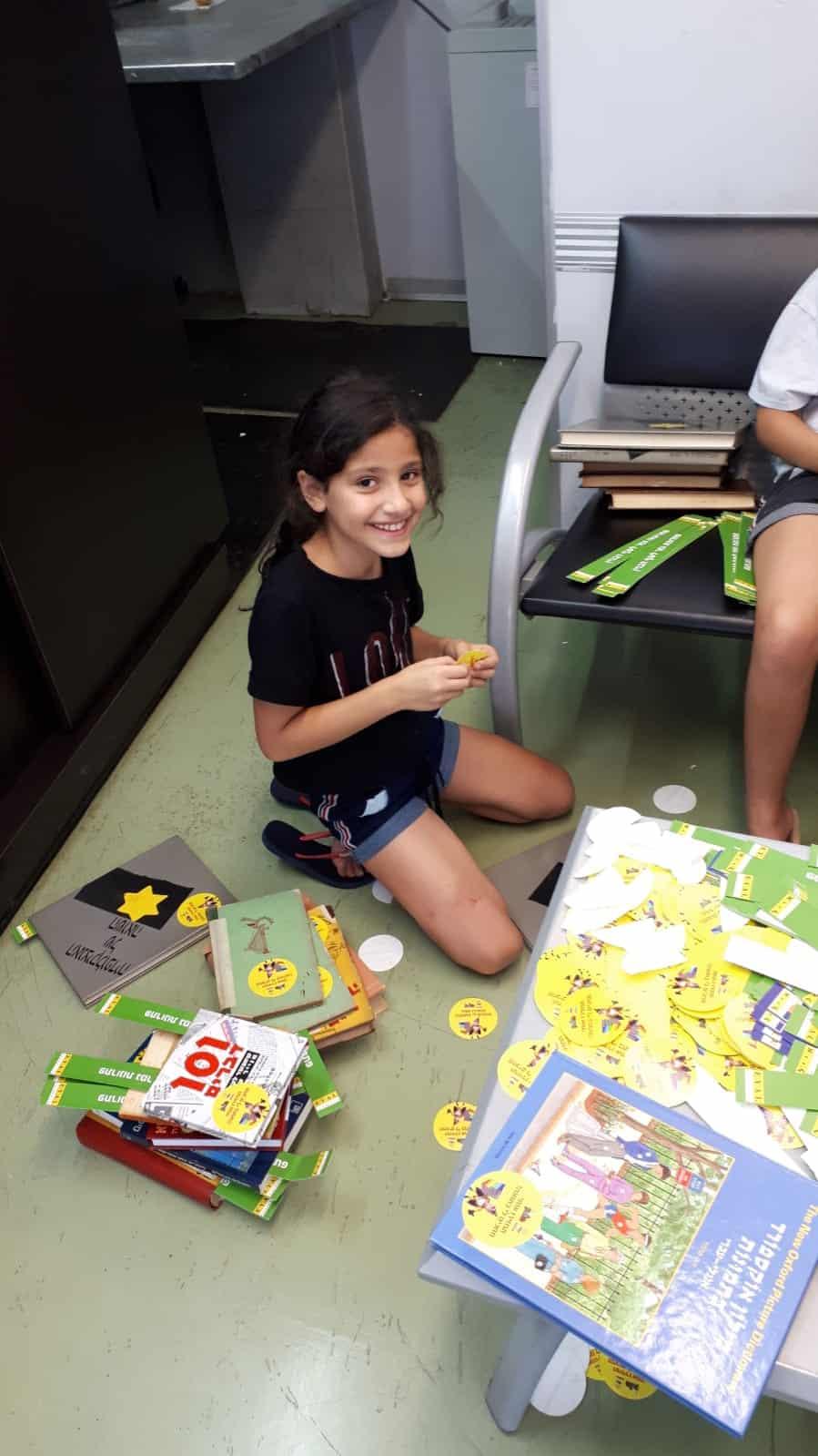 ילדי משפחת קרוטהמר ממתנדבי סניף רוטרי חולון מטפלים בספרים, צילום:-מוטי קרוטהמר